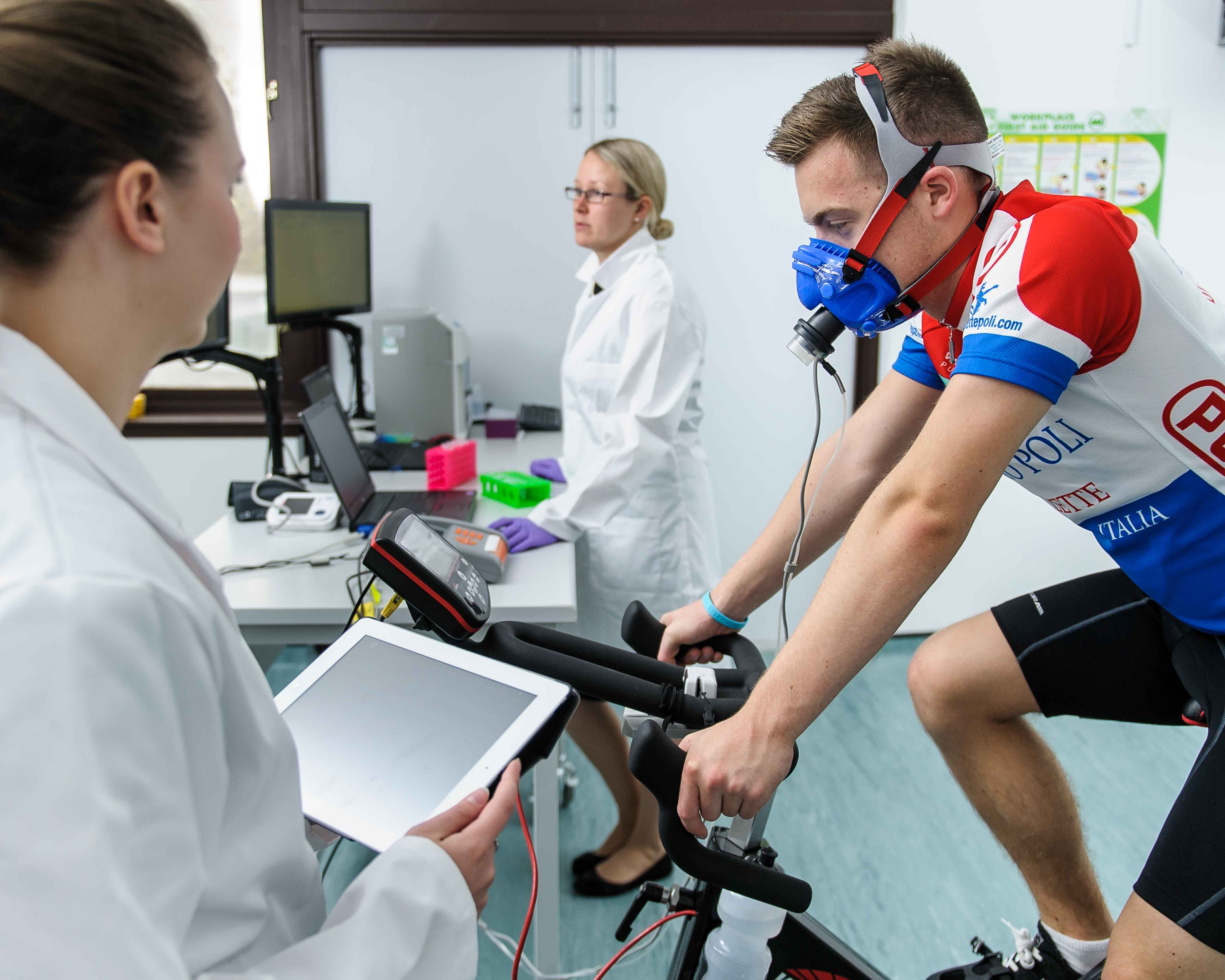 This image shows a man wearing a breathing mask whilst using an exercise bike and being monitored by scientists.