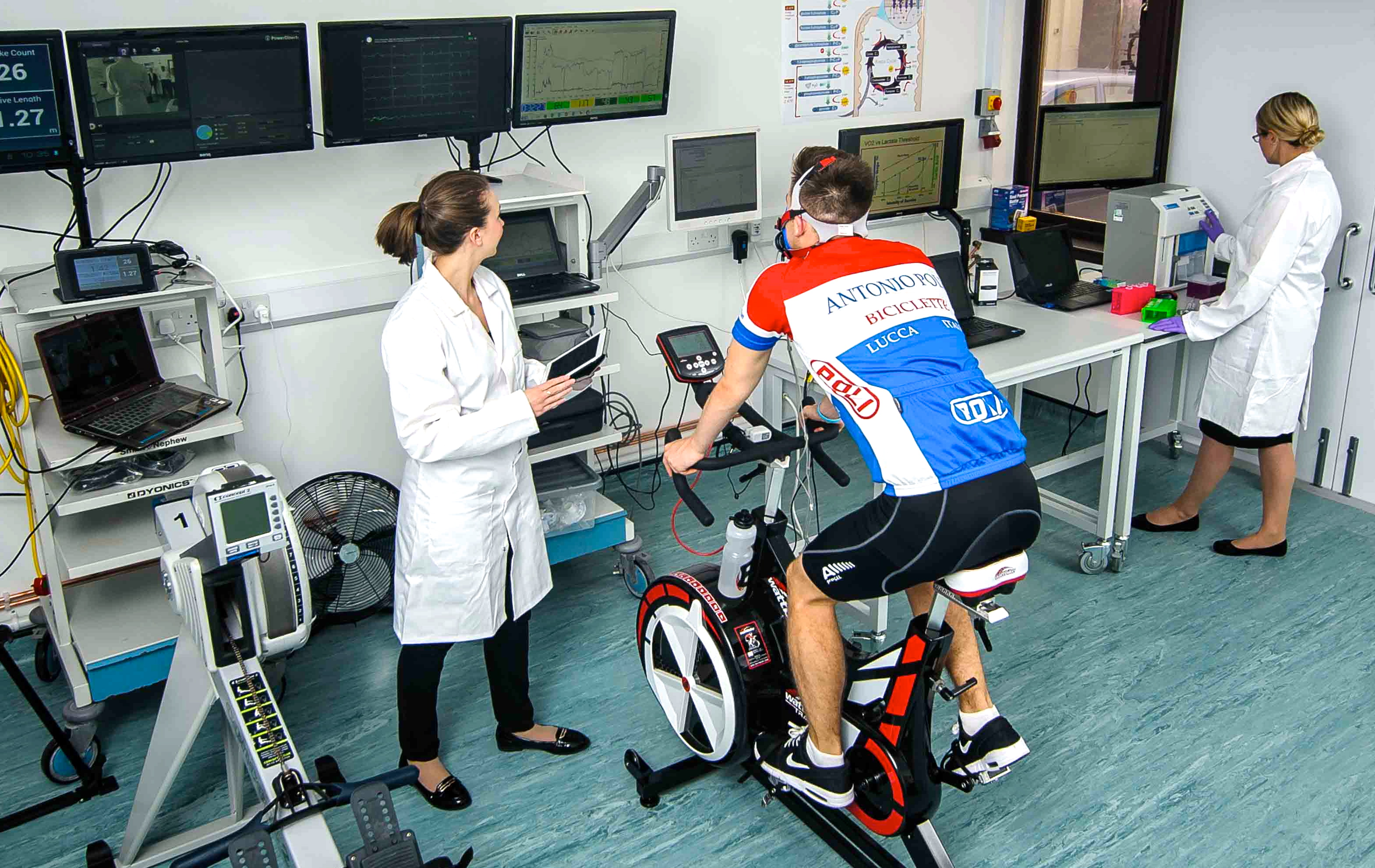 This image shows a young man working on an exercise bike in a laboratory and being monitored by a scientist.