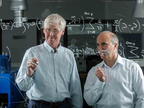 This image shows two scientists working through a complex mathematical formula written on a glass screen.